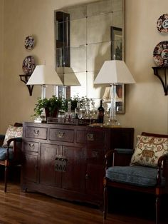 This sideboard adds a timeless touch and has plenty of room to store bar essentials. Mirror tiling and tall glass lamps complete this eclectic presentation.