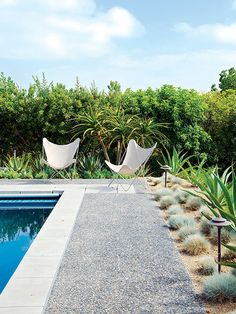 Two chairs are all that are needed to make this backyard swimming pool comfortable for guests, as the gorgeous plants and landscaping do most of the design work.