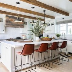 BECKI OWENS- 7 Elements of the Modern Farmhouse. White kitchen with warm rustic wood, industrial lighting, and exposed beams.