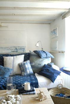 Sofa piled high with indigo cushions and natural with blue stripe cushions, create the look at home