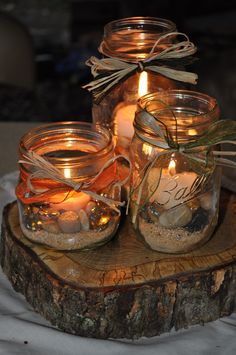 Our centerpieces..created by myself and my Maiden of Honor Sherri Parsons Mace... Very simple..oak slab, mason jars, raffia, ribbon, candles and sand and stones. They were perfect!