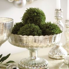 Fill your decorative bowls and flower vases with lush green color and organic texture for the holidays and all year-round with our Preserved Cypress Sphere. This pretty topiary ball is made of natural cypress boughs that have been specially preserved to keep their deep emerald green color season after season. Add indoor greenery as tabletop decor or mantle decor for a pop of color. #IndoorGreenery #GreeneryBall #RoundPlant #TabletopGreenery