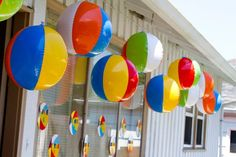 The uses for beach balls in a surf themed party are endless!  Here simple plastic beach balls are made into a hanging garland.