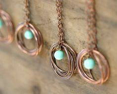 Oxidized copper trinity ring necklace with vintage Japanese glass baby blue bead. Hand forged by me! to interlock to create an organic and rustic necklace from copper wire. The necklace hangs from a copper chain. Each ring is about 1 in diameter. Copper Rings, Copper Jewelry, Wire Jewelry, Jewelry Crafts, Beaded Jewelry, Handmade Jewelry, Copper Wire, Copper Necklace, Flower Jewelry