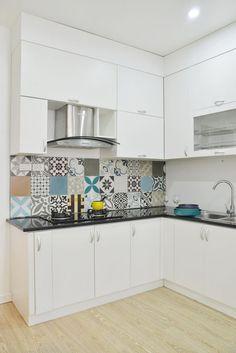 kleine Küche mit weißen Küchenfronten, schwarze Arbeitsplatte und gemusterte Fliesen