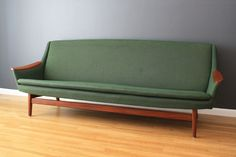 "Scandinavian Modern Sofa    This vintage Mid-Century sofa has the original green upholstery and teak accents. It is in great condition with age appropriate wear. This sofa has been professionally cleaned using green products.  Measurements:  33""H top, 17""H seat, x 86.75""L x 26""deep"
