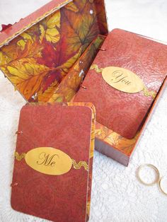 This Wedding Vow books and box set are the perfect touch for your wedding. The one-of-a-kind keepsake box is decorated with a beautiful Burgundy with a Gold glittered design paper and coordinating fabric leaves and paper flower embellishment. The box is edged in a gold ric-rac and can be personalized with your names and date or favorite quote. The inside of the box is covered in a beautiful fall leaf design in shades of gold, red, yellow, orange and burgundy.  The matching set of…