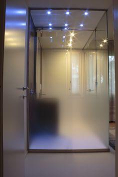 Bagno in camera con pareti in cristallo. Doccia con cromoterapia
