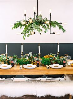 Modern table design with simple greenery woven throughout the table and industrial light fixture. #holidays #cokestyle Thanks to our friends at Coca-‐Cola!