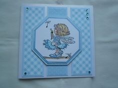 3 equal panels of patterned blue papers matted on plain blue placed evenly on front of square card. LOTV fairy image coloured with Pro-markers matted on layers of blue patterned & plain card cut with Spellbinders octagonal die. Decorated with pale blue gems