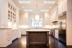 Gorgeous kitchen features lattice skylights over a warm brown center island…