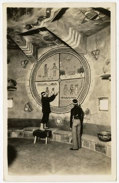 Postcard (black and white, Real Photo); two Hopi men, including Fred Kabotie (back to the camera) in a room with murals painted by Fred Kabotie in the  Desert View Watchtower; both men wear traditional clothing and ornament; Desert View Watchtower, Grand Canyon, Arizona, USA.  Printed. British Museum, Online Collection.