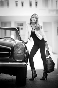 Black and white. Girl posing with a classic Mercedes sports car