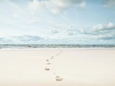 Footprints Leading Into Sea Photograph