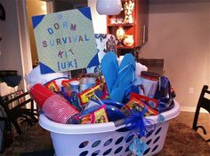 """Here is the graduation gift basket that I made for my baby sister last week. It's a """"dorm survival kit""""- complete with ramen, towels, bedding, dorm decoration items, and lots of little fun things that every college student needs. I liked the idea of building the """"basket"""" in a laundry bin- useful!"""