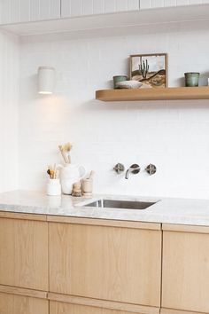 Like the blonde wood, matte white handmade look tiles, the light grey stone bench top, the grooved cupboards above, and the floating shelf Timber Kitchen, Kitchen Benches, Kitchen Interior, Kitchen Decor, Kyal And Kara, Timber Shelves, Interior Desing, Studio Kitchen, Kitchen Cabinetry