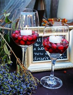 Wine glasses with cranberries and floating candles.