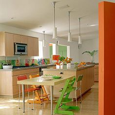 A Playful Palette   Sleek lines and neutral wood tones clear the way for fruit-basket shades of yellow, orange, and green in this kitchen's fun and functional decor. Mismatched chairs surround a lowered surface ideal for snacks or homework. Modern white pendants keep the mood -- and atmosphere -- bright.