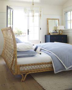 This elegant bedroom has a coastal feel with its brass chandelier, rattan mirror, raffia dresser, and rattan bed. Coastal Master Bedroom, Coastal Bedrooms, Bedroom Decor, Bedroom Ideas, Blue Bedrooms, Bedroom Modern, Master Bedrooms, White Bedroom, Bedroom Inspiration