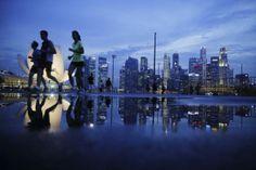 Joggers run past the skyline of Singapore's financial district April 21, 2014. REUTERS/Edgar Su