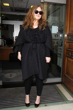 Adele masters the all-black look, belting a textured coat over skinny jeans and adding a pair of cat-eye sunglasses