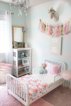 Toddler girl bedroom updates with a few sweet touches. We added a toddler Jenny Lind bed, a new chandelier, gold bedding, a floral blanket, and a shabby chic shelving unit to add a few new big girl touches to our daughters room. #toddlerroom #girlsroom #nurserydecor #shabbychic #mint #gold #etsy #stripedwall #interiorpaint