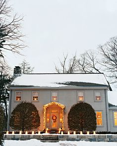 The summer house on Martha's Bedford, New York, property is where the farm's original owner spent the warm months. At dusk, the facade is illuminated with candles and lights.
