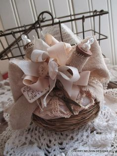 Nesting Instincts - rustic pincushion in a bird nest basket, adorned with a doily, muslin cloth, wooden spools and ribbon.