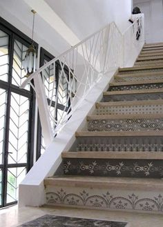 These Moroccan-inspired motifs have traditional roots, but how modern they look in this all-white setting, with a dramatic architectural stair railing and windows with striking herringbone grillwork. The hand-stenciled motif is from Royal Design Studio.