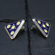 These cloisonné-enameled earrings with a simple, triangular form, are decorated with opaque, cobalt blue and yellow colored enamels. For…