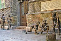 """A Pál utcai fiúk szobra. (Sculpture of the Boys of the Pál Street) Budapest VIII. kerület Práter utca 11. """"Hát csak jöttek a Pásztorok, egyre közelebb jöttek, és nézték nagyon a golyókat. Mondom a Kolnaynak: Te, ezeknek tetszik a mi golyónk - és még a Weisz volt a legokosabb, mert ő mindjárt mondta: Gyönnek, gyönnek, ebből a gyövésből nagy einstand lesz"""" (Molnár Ferenc: A Pál utcai fiúk)"""
