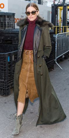 Olivia Palermo wore a burgundy turtleneck sweater, suede midi skirt with a brown belt, olive booties, and a long olive green fur trench coat.