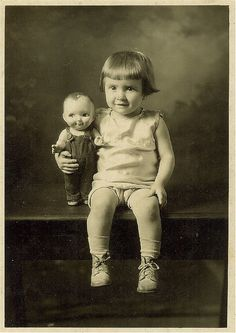 Child with a doll that looks a little like her. Cute!