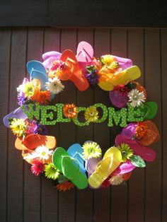 Cutest Flip Flop Wreath Ive seen! The wreath is a grapevine wreath from Hobby Lobby, wood letters from Hobby Lobby are painted, flowers came from Hobby Lobby, and one dollar flip flops from Old Navy
