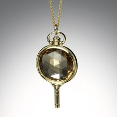 """This Monica Rich pendant is inspired by turn of the century men's pocket watch keys.A perfect everyday piece that can be worn alone or layered, with a beautiful champagne quartz center and cabochon moonstone accent.The pendant hangs on an 18k yellow gold 26"""" wheat chain. Pendant measures 1.7"""" long with bail."""