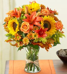 Fields of Europe™ for Fall. Imagine spending a perfect autumn day browsing the bustling flower markets of Europe. It's easy with this arrangement of orange roses and lilies, vibrant sunflowers, poms and more hand-gathered in a glass gathering vase and finished off with raffia ribbon. They'll cherish it like a keepsake from a trip they've yet to take. Save 20% with the coupon code ABENITY at http://www.1800flowers.com.