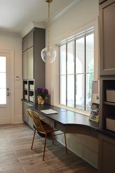 A Katie Pendant with Acorn Glass hangs over a curved gray built-in desk topped with honed black granite paired with a gold metal chair tucked under a large paned window.
