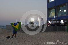 Man waving Brazilian flag in front of media center on Copacabana beach during Rio2016 Summer Olympic Games in Rio de Janeiro, Brazil. Photo taken on Aug 5th, 2016