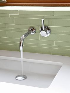 Here, a sleek wall-mount faucet mingles with the modern simplicity of green rectangular tile, not the color so much...the tile size-varying