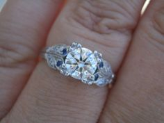 Vintage setting with sapphires and fishtail prongs in center.