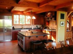 Timber frame home kitchen with steel appliances and dark stained wood