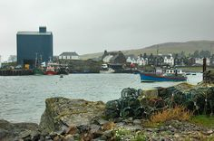 A view of Islay's main harbour in Port Ellen on a grey and damp day. Several fishing boats are waiting for their next outing at the pier. On the right a former lifeboat which was based on Islay for...