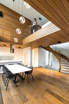 Drewniane schody, drewniany sufit, biała kuchnia, dwukondygnacyjna jadalnia, żarówki Edisona. Minimalistyczny nowoczesny dom jednorodzinny. Elewacja drewniana połączona z płytą elewacyjną. Szklane barierki balustrady, duże okna bez szprosu w narożniku.