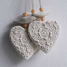 A semi porcelain wall hanging. Heart and hand sculpted bird. The heart has been impressed with floral decoration and the small bird has incised wings