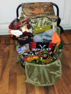 Hunting Raffle Basket - Camo backpack zip tied to a RealTree seat. Backpack is filled with a small lantern, glow sticks, beef jerky, peanuts, gloves, socks, camo hat, blaze orange stocking cap, bug spray, scent block spray, camo face paint, poison ivy stick, and multi-survival tool.