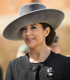 Crown Princess Mary, in a grey asymmetrical brimmed hat designed by Susanne Juul. The felt hat has a flat crown and upturned 'slice' brim