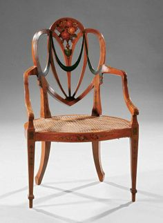 An Edwardian Satinwood And Paint-Decorated Armchair In The Adam Taste, Shield-Shaped Back With Floral Splat, Drapery Swags And Bellflower Decoration, Serpentine Seat Rail, Caned Seat, Tapering Square Legs Ending In Spade Feet - Liveauctioneers