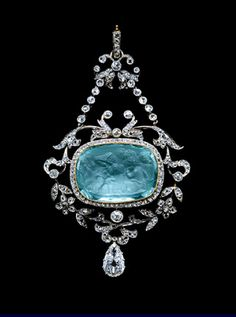 The aquamarine cameo with facetted back represent four Cupids (putti) playing the part of vintagers...Mounted as a pendant within a rose diamond mille-grain border, hanging within an open frame of floral and leafy branches with a pear shaped diamond hanging below, it is attached by chains to the trumpet shaped flower heads and the suspension loop at the top, all diamond set. Cameo: 18th century style. Pendant: 1905. (re-pin)