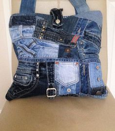 Handmade tote handbag is made from an assortment of recycled jeans fabrics. On the front of the bag I have used jeans belts and denim patches also a ring to display your favourite key ring or bag charm. On the reverse side of the bag I have used two recycled jeans pockets (as shown in