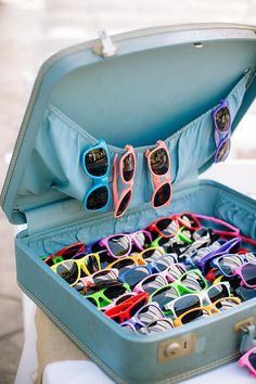 bright sunglasses wedding favors in vintage suitcase @myweddingdotcom